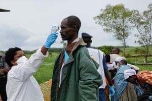 A medic measures a man's temperature on his arrivalin Burundi from the Democratic Republic of Congo.