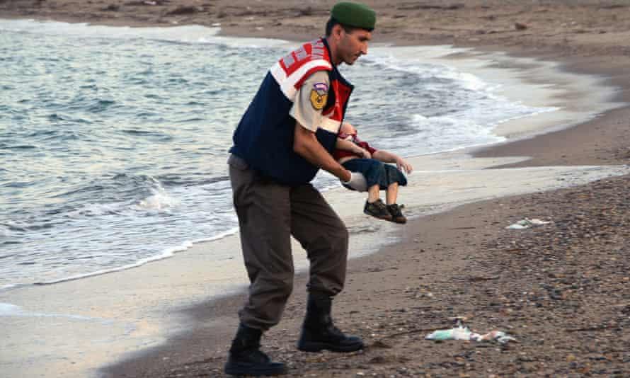 Police officer carries the body of Alan Kurdi on a beach