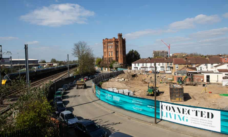 A building site in front of suburban homes and a crenelated Victorian building with railway to the left and a sign saying Crossrail arrives in 2019