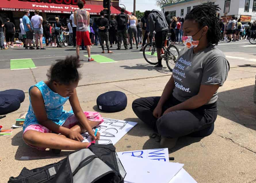 Zenzele Isoke supplied sign-making materials at the protest and helped Judeah Reynolds, nine, with her sign in Minneapolis on Thursday.