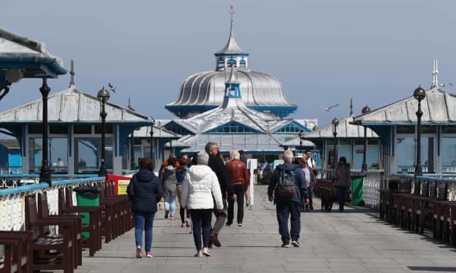 People walk along the pier in Llandudno, Wales on Monday.