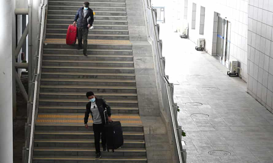 Passengers wearing face masks walk down the stairs after getting off a train at the railway station in Macheng, Hubei