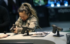 A woman looks at a handgun at the Glock booth.