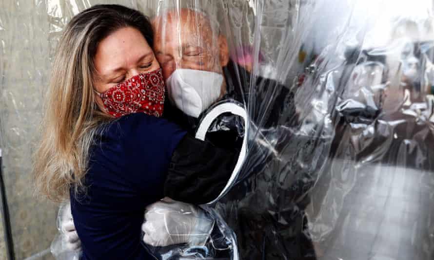 Maria Paula Moraes hugs her father through a 'hug curtain' in São Paulo, Brazil, in July.