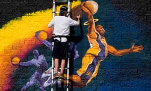 Artist Kiptoe helps paint a mural as a memorial to Kobe Bryant in West Hollywood, California.