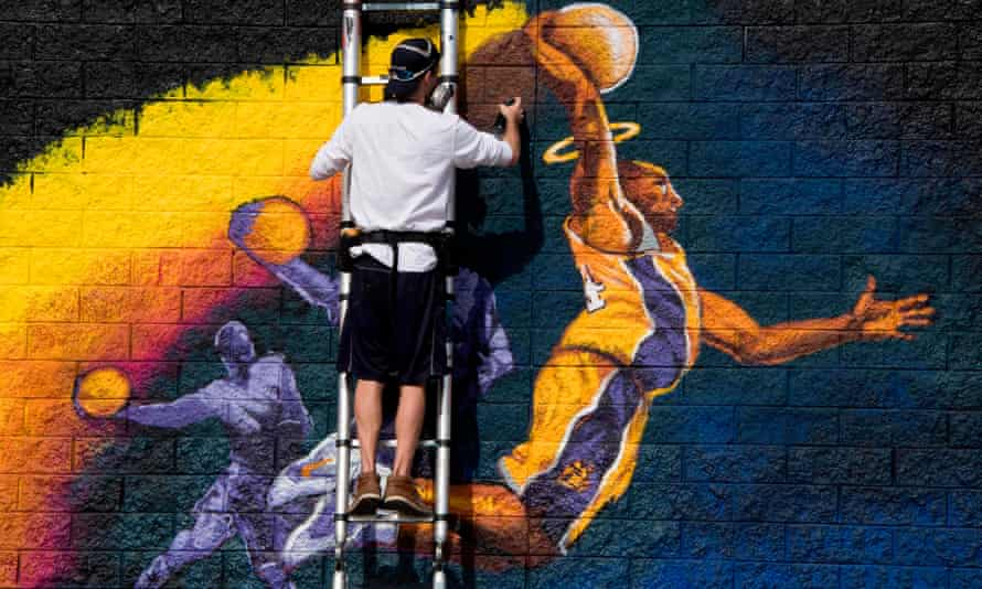 Artist Kiptoe helps paint a mural as a memorial to Kobe Bryant in West Hollywood, California.