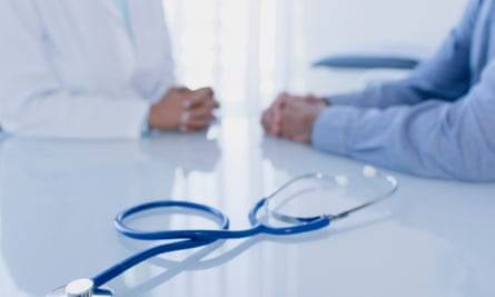 Stethoscope on white desk in doctors office, female doctor and patient sitting in background