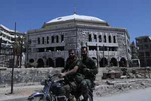 Syrian soldiers ride on a motorcycle in front of the grand mosque.