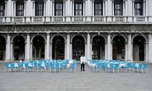 A waiter stands by empty tables outside a restaurant at St Mark's Square, which is usually full of tourists, after Italy's government adopted a decree with emergency new measures to contain the coronavirus, in Venice, Italy, March 5, 2020.