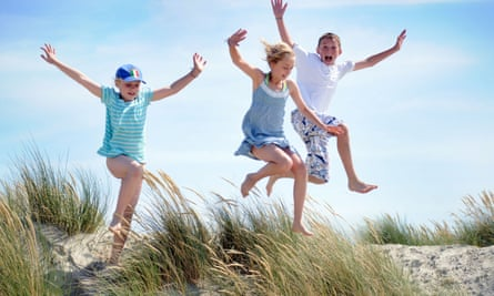 Royalty free photograph of boy and girl jumping off sand dunes on beach in the summer on the British coast UK<br>BDBK2R Royalty free photograph of boy and girl jumping off sand dunes on beach in the summer on the British coast UK
