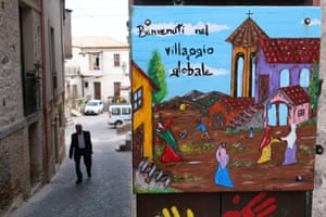 A sign in Riace reading 'Welcome to the Global Village', put up before Italy's new far-right government cracked down on the town's pro-immigration model.