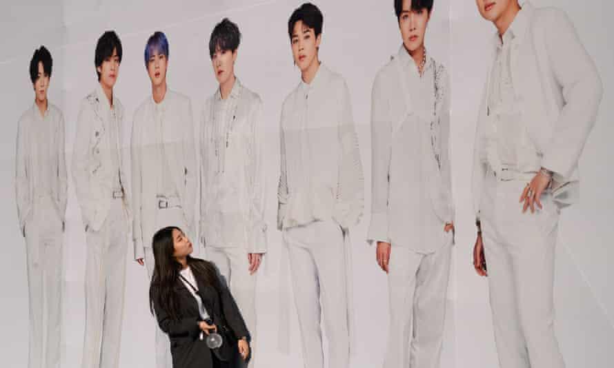 A fan poses against a backdrop of K-Pop boyband sensations BTS.