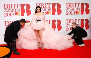 Two men help Dua Lipa, nominated 5 categories, with her dress as she poses for photos