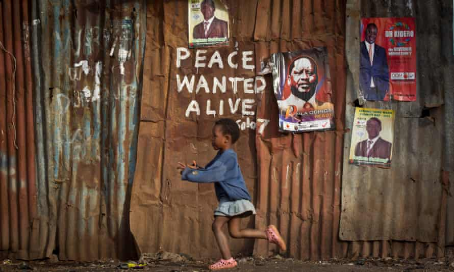 A young black girl runs past rusted corrugated metal shacks in Kibera slum, Nairobi
