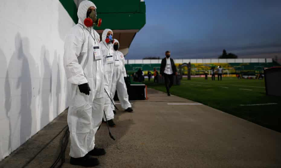 A coronavirus disinfection team stand ready during a match in Group G of the Copa Libertadores, between Defensa y Justicia from Argentina and Delfin of Ecuador, in Florencio Varela, Argentina