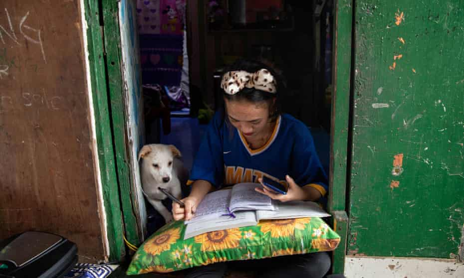 Annie Sabino, 16, tries to do her school work while working at her family's food stall in the Philippines in January.