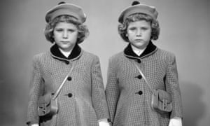 Twin girls in hats and coats wearing white gloves, circa 1950s.