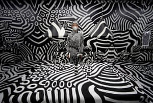 Tokyo, Japan. A model poses for photographs within Seen behind watching, an installation by the artist Shigeki Matsuyama at a design trade show