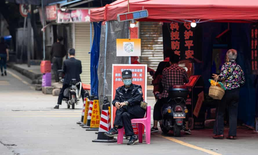 A security guard sits next to the checkpoint near the entrance of Yaotai, an area close to the African Village in Guangzhou.