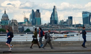 People cross Waterloo bridge with the City of London skyline in the background