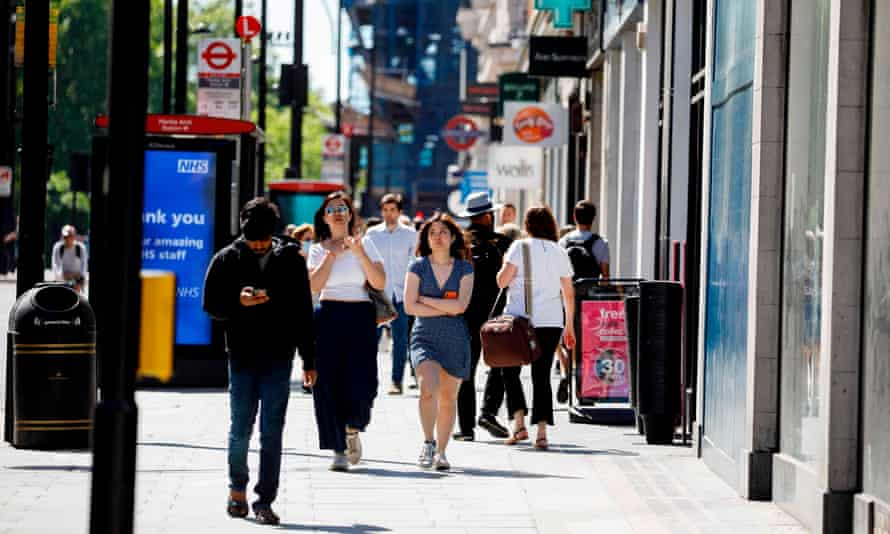 People walk past closed shops on Oxford Street in London