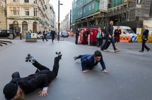 Dancers dressed as stockbrokers perform on rollerskates outside Lloyds of London