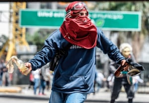 An activist clashes with riot police during a protest in Caracas against Venezuelan president Nicolás Maduro.