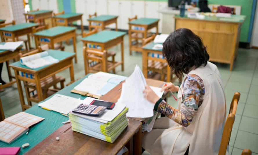 A teacher marking her pupils' work.
