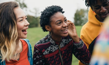 Close up shot of young women talking to their friends in a public park.