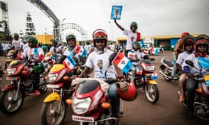 Moto taxi drivers hold flags of the governing Rwanda Patriotic Front at the start of a parade in Kigali.