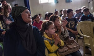 Refugees at the Zataari camp watch Hamlet