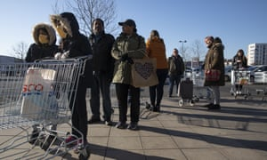 Shoppers queue outside a supermarket in London, 23 March 2020