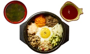 Bibimbap beef dish, divided into sections with an egg in the middle, and two side dipping dishes