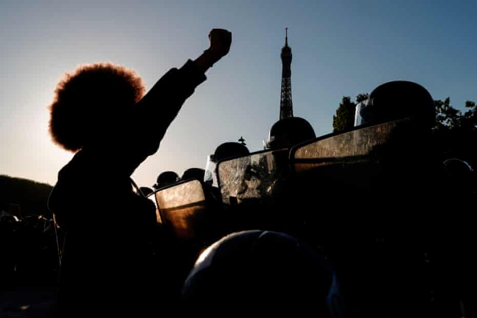 People raise their fists in front of riot policemen during a protest at the Champ de Mars, with the Eiffel Tower in background, in Paris in June 2020.