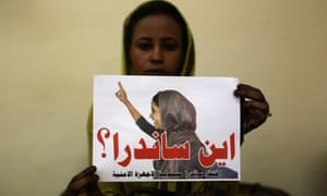 "A supporter of Sudanese opposition activist Sandra Faroug Kadouda holds her photo, with the message ""Where Is Sandra"" in Arabic."