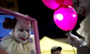 A person dressed as a diabolical clown prepares for the start of the Zombie Walk in La Paz