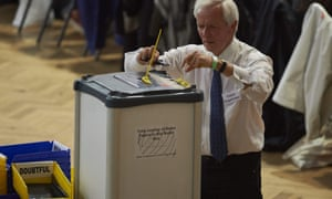 A counting supervisor opens a ballot box  at The Royal Horticultural Halls in central London