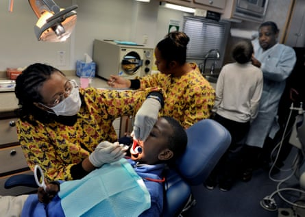 Dr Belinda Carver-Taylor (left) cleans a child's teeth inside her mobile surgery, The Deamonte Driver Dental Project.