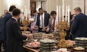 Football players eating from the fast food buffet.