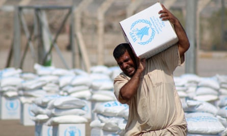 A displaced Iraqi collects boxes of food donated by the World Food Program.