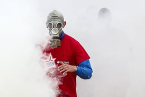 A member of a youth sports organisation supported by the military wears a gas mask as he competes in an obstacle course race at Patriot park, Moscow.