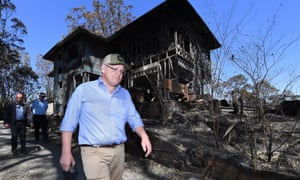 Scott Morrison walks past a burnt-out house during a visit to the bushfire-affected area of Binna Burra in the Gold Coast hinterland.