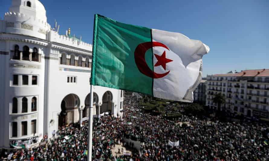 An Algerian flag flies over demonstrators protesting against President Abdelaziz Bouteflika in Algiers