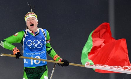 Darya Domracheva skis with a Belarus flag over the finish line at the Winter Olympics.