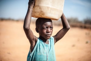 Orlando David Valoi, eight, walks several milies in Mabalane district to collect water from a borehole. Dropout rates in Mozambique's schools have risen dramatically as more children have to forage for food and water
