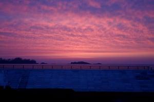 The sun rises over a seawall at a beach in Kesennuma, Miyagi prefecture