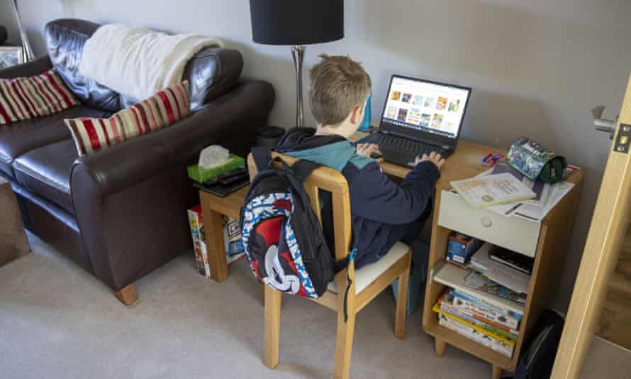 A young student working on a computer at home