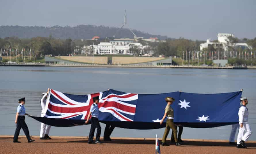 Defence force personnel march with the Australian flag during an Australia Day citizenship ceremony in Canberra earlier this year.