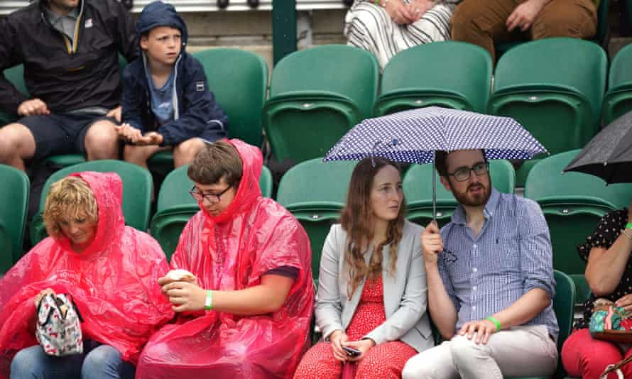 Penonton berlindung dari hujan pada hari keenam Wimbledon