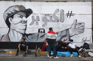 Young protesters rest under a mural in Baghdad's Tahrir Square on 8 November 2019 as the capital braces for another day of anti-government demonstrations. The graffiti celebrates the month in which the protests began, declaring simply 'October!'.